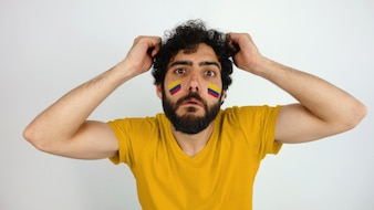 Sport fan with the flag of Colombia makeup on his face disappointed with his team
