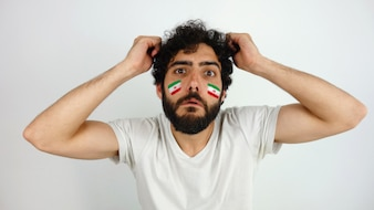 Sport fan with the flag of Iran makeup on his face disappointed with his team