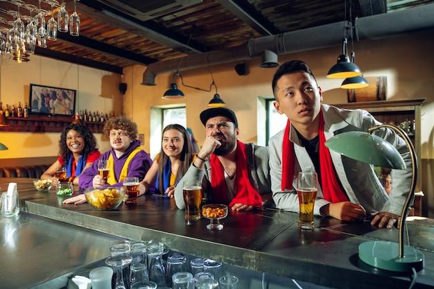 Любители спорта аплодируют в баре, пабе и пьют пиво во время чемпионата, соревнования идут. многонациональная группа друзей взволнована просмотром перевода. человеческие эмоции, выражение, поддерживающая концепция.