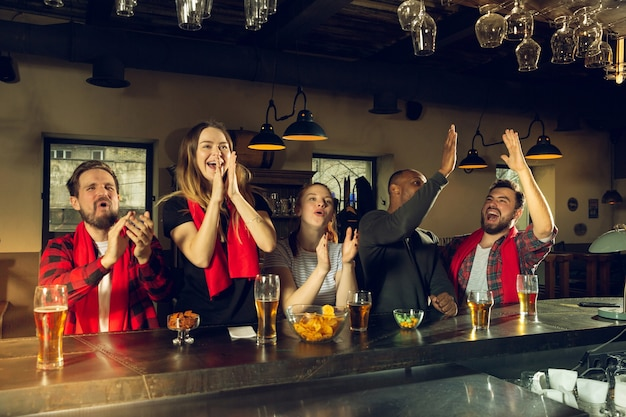 Sport fans cheering at bar pub and drinking beer while championship competition is going