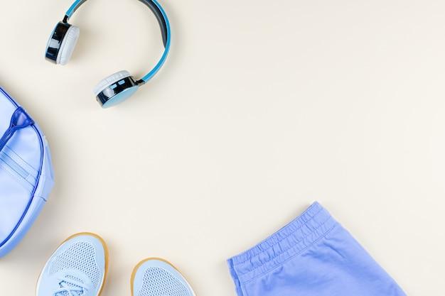 Квартира спортивной моды лежала с наушниками, кроссовками, одеждой. копировать пространство