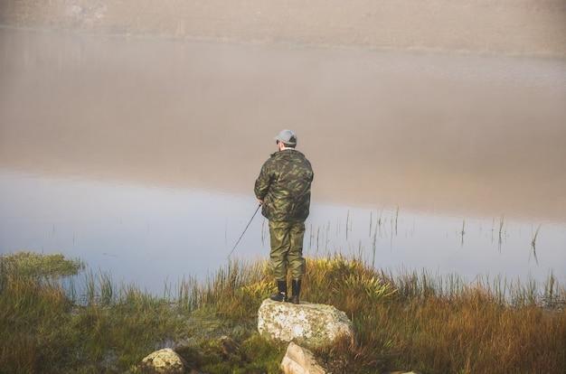 曇りの日に湖で釣りをするスポーツ漁師。
