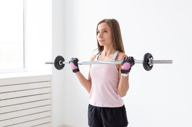 스포츠, 피트니스 및 사람들이 개념-그녀의 팔뚝을하고, 무게 막대와 맞는 젊은 여성 운동.