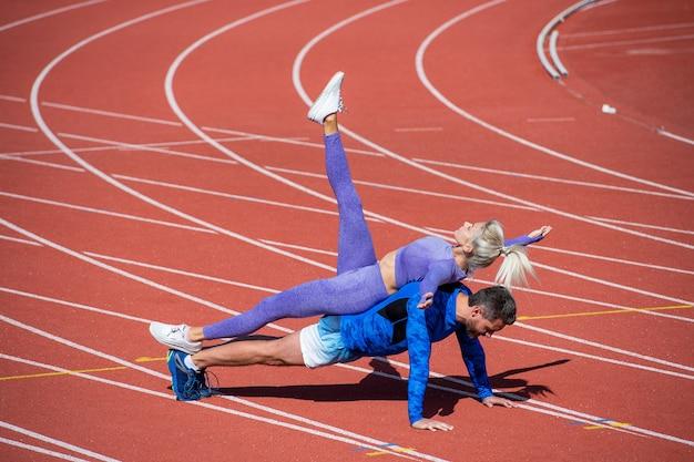 스포츠 피트니스 커플 훈련은 함께 판자 위에 서서 운동복, 스포츠 및 피트니스를 입고 야외 경기장 경마장에서 밀어 올립니다.