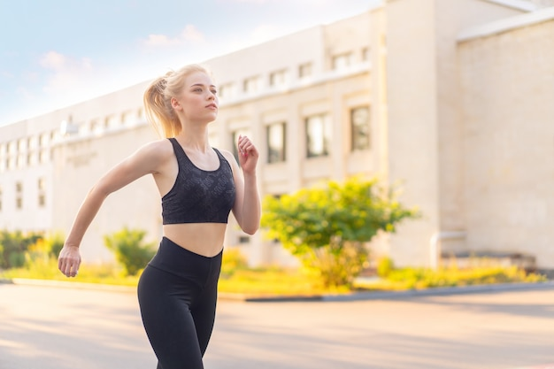 Sport and fitness. fit woman running city street summer sunny morning caucasian athletic female jogging outdoor cardio training active healthy lifestyle dressed black sportswear motivation concept