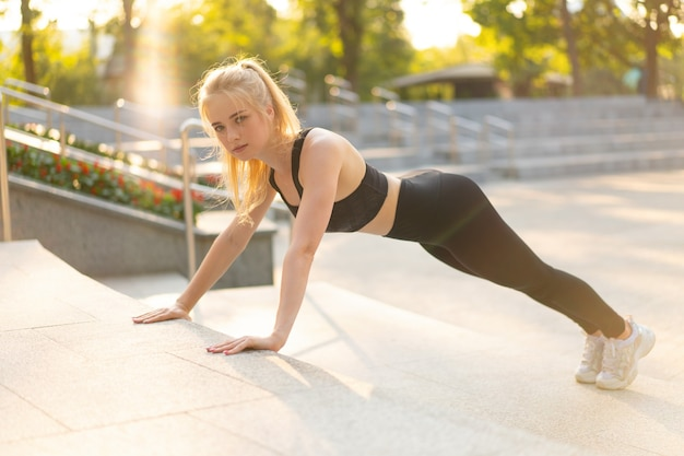 Sport and fitness fit young adult woman doing plank exercise outdoor urban environment. sunlight summer park caucasian ahlrtic female morning workout training exercises endurance abs muscle