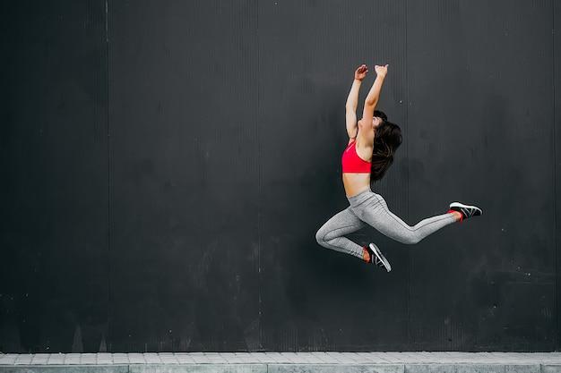 Sport fitness girl in fashion sportswear jumping in the street.