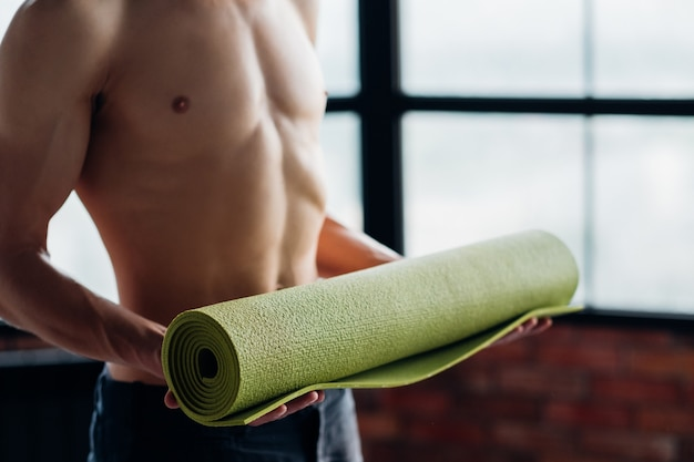 Sport fitness and gym training. taking care of your body health. man holding yoga mat prepared to excersise.