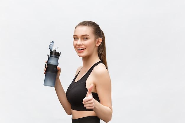 スポーツ、フィットネス、ライフスタイル、人々のコンセプト-ウォーターボトルを持った幸せなスポーティーな女性。