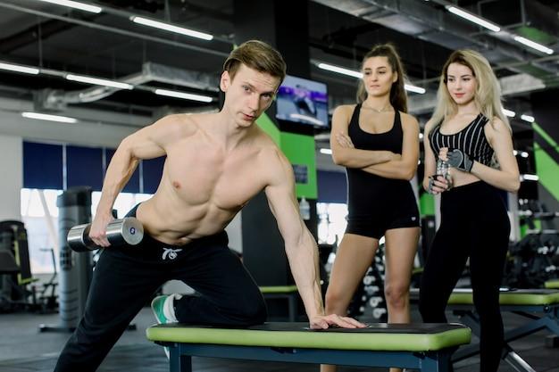 스포츠, 피트니스, 라이프 스타일과 사람들 개념-체육관에서 아령으로 근육을 flexing 젊은 남성 피트니스 트레이너. 배경에서보고 두 어린 소녀