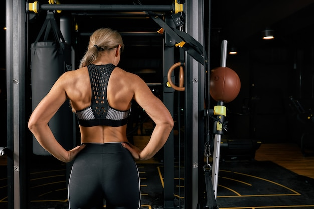 Sport, fitness, lifestyle and people concept. woman exercising and doing pull-ups in gym from back