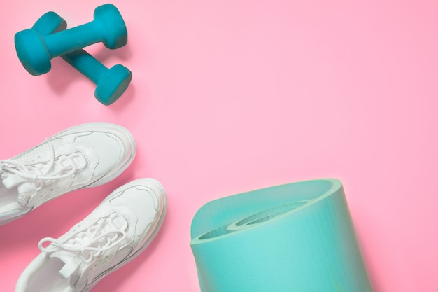 Sport and fitness shoes, dumbbell, yoga mat on pink.