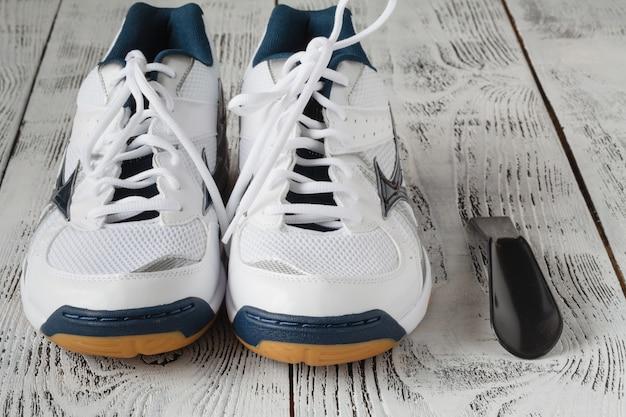 스포츠, 피트니스, 신발, 신발 및 개체 개념-나무 바닥에 운동화의 닫습니다