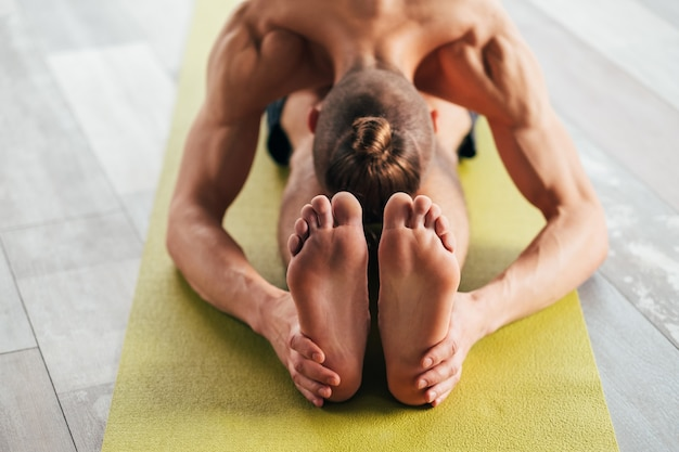 Sport fitness and stamina training. physical activities for strong body and healthy mind. man exercising on yoga mat on the floor.