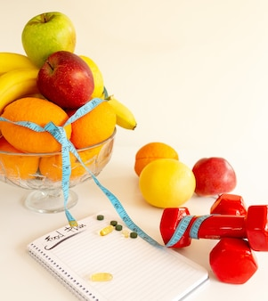 Sport and fitness supplements science vs natural fruits , notebook .healthy lifestyle concept. food plan