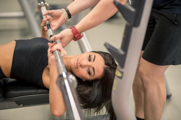 Спорт, фитнес, работа в команде, бодибилдинг и люди концепции - молодая женщина и личный тренер с штангой сгибание мышц в тренажерном зале