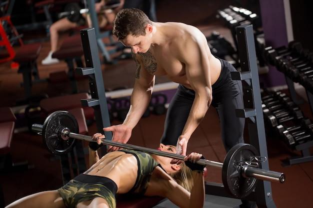 スポーツ、フィットネス、チームワーク、ボディービル、人々のコンセプト-ジムでバーベルを曲げる筋肉を持つ若い女性とパーソナルトレーナー