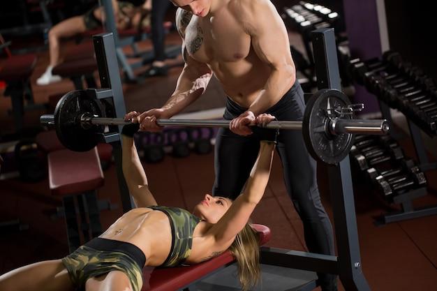 Спорт, фитнес, работа в команде, бодибилдинг и люди концепции - молодая женщина и личный тренер со штангой, разгибающей мышцы в тренажерном зале