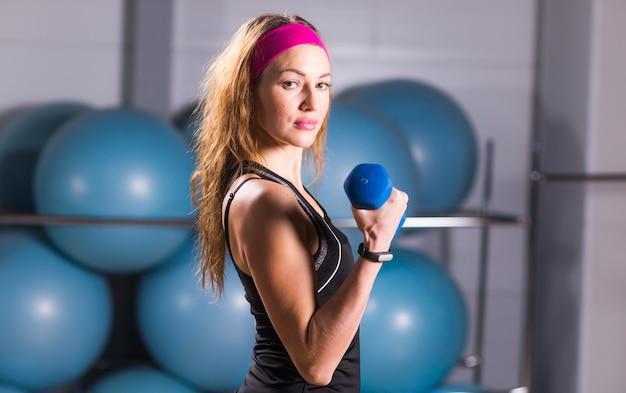スポーツ、フィットネス、トレーニング、幸福の概念-水色のダンベルでスポーティな女性の手。