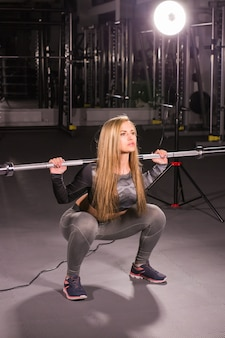 스포츠, 피트니스, 교육 및 행복 개념-체육관에서 바벨 스포티 한 여자