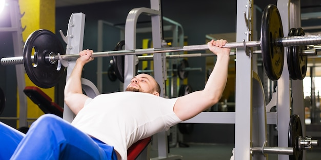 Sport, fitness, training and people concept - man during bench press exercise in gym.
