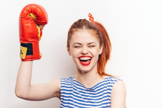 Sport fitness women in boxing gloves and striped t-shirt emotions model.