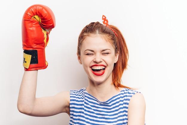Спортивные женщины фитнеса в боксерских перчатках и полосатой футболке модели эмоций.