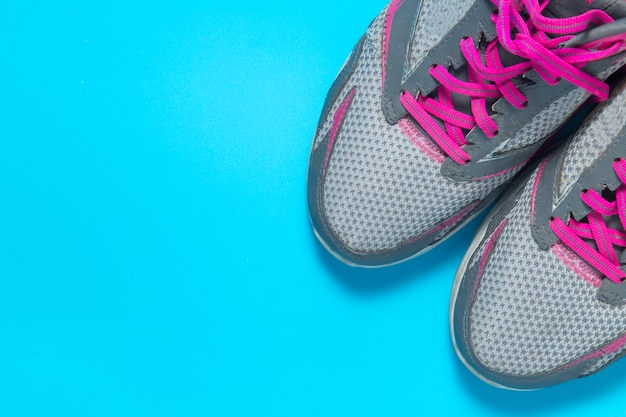 Sport flat lay pink shoes on blue background with copyspace.