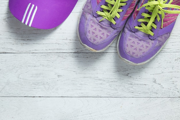 Sport flat lay purple shoes and cap on white wooden background.
