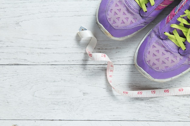 Sport flat lay purple shoes and measuring tape. concept healthy lifestyle and diet.