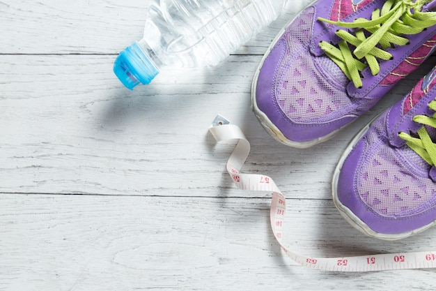 Sport flat lay purple shoes and measuring tape on white wooden background.