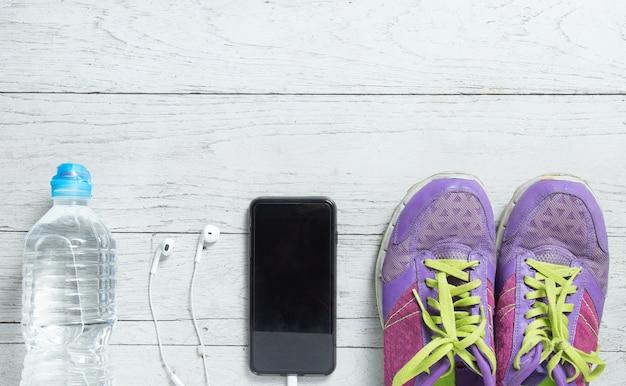 Спортивная плоская легкая фиолетовая обувь, смартфон и оборудование для тренировки.