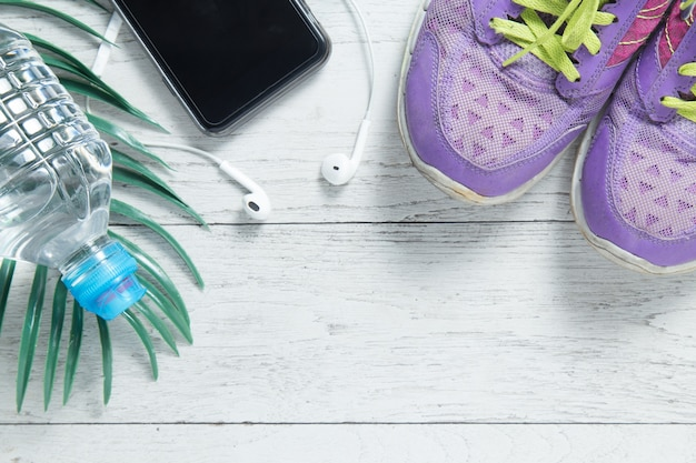 Sport flat lay purple shoes, smartphone and workout equipments.