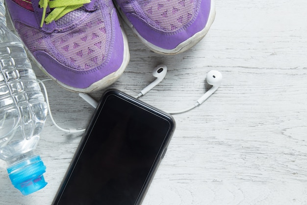 Sport flat lay purple shoes, smartphone and workout equipments
