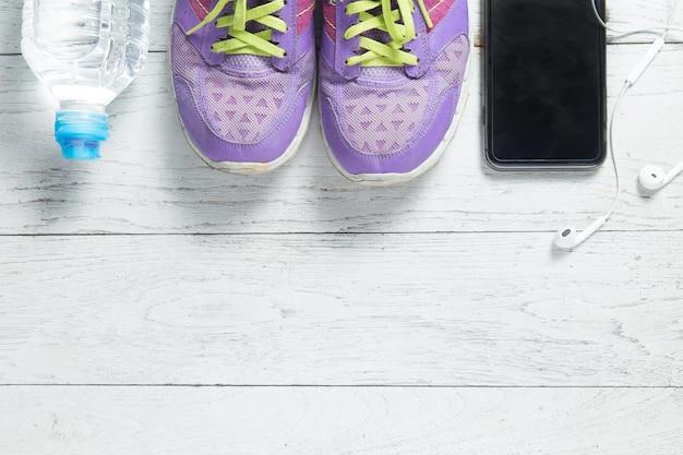Спортивная плоская обувь, смартфон и оборудование для тренировок.