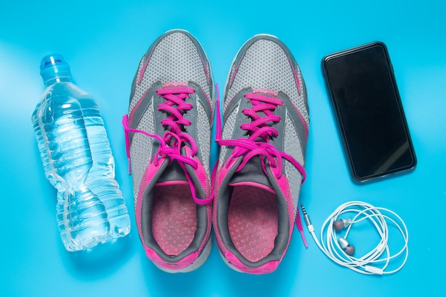 Sport flat lay shoes with water bottle, smartphone, earphones.
