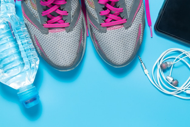 Sport flat lay shoes with water bottle, smartphone, earphones.