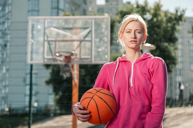 여성을위한 스포츠. 그녀의 손에 공을 서있는 동안 당신을 찾고 매력적인 낚시를 좋아하는 여자