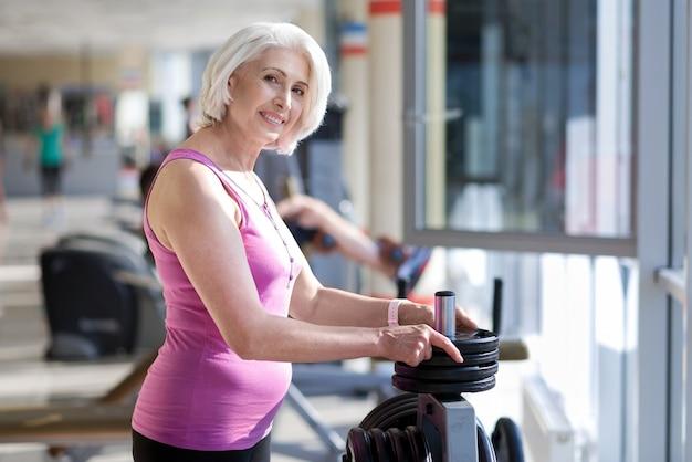 Спорт навсегда. очаровательная счастливая старшая женщина улыбается и трогательно тарелки, стоя возле штанги.