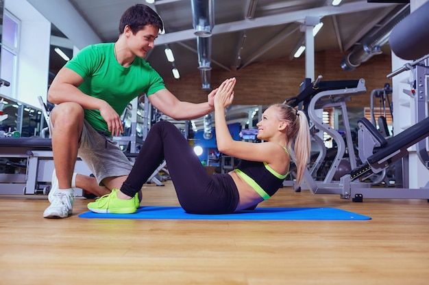 체육관에서 바닥에 트레이너 남자와 복근 운동을하는 스포츠 소녀.
