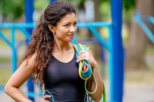 Спортивная девушка держит в руках красочные эластичные резинки на открытом воздухе. довольно молодая женщина с портретом фитнес-оборудование