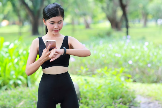 Sport girl holding smart phone and checking smart watch