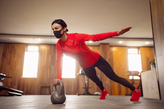 Sport girl in mask from coronavirus doing kettlebells planking