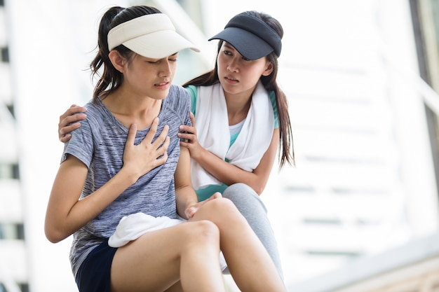 Sport girl try to help her friend who having a heartache while jogging in the city.