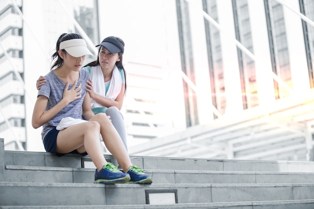 Sport girl try to help her friend who is having a heartache while jogging in the city.