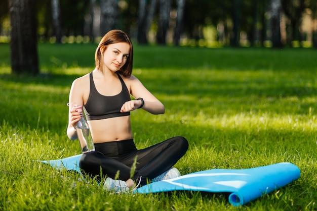 Ragazza sportiva utilizzando fitness tracker o monitor della frequenza cardiaca in possesso di una bottiglia di acqua