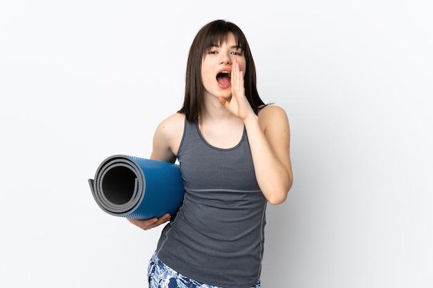 Спортивная девушка с циновкой изолирована на синем кричит с широко открытым ртом
