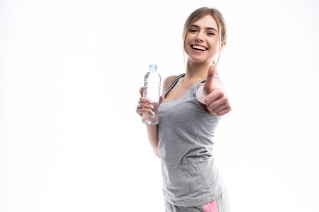 Девушка спорта с водой и большим пальцем руки выставки вверх изолированный на белизне.