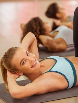 Sport girls smiling while working out lying on yoga mat.
