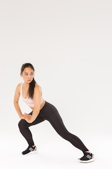 Sport, gym and healthy body concept. full length of focused brunette asian girl doing stretching exercises, female athlete warm-up before running training, looking away and bending knee.